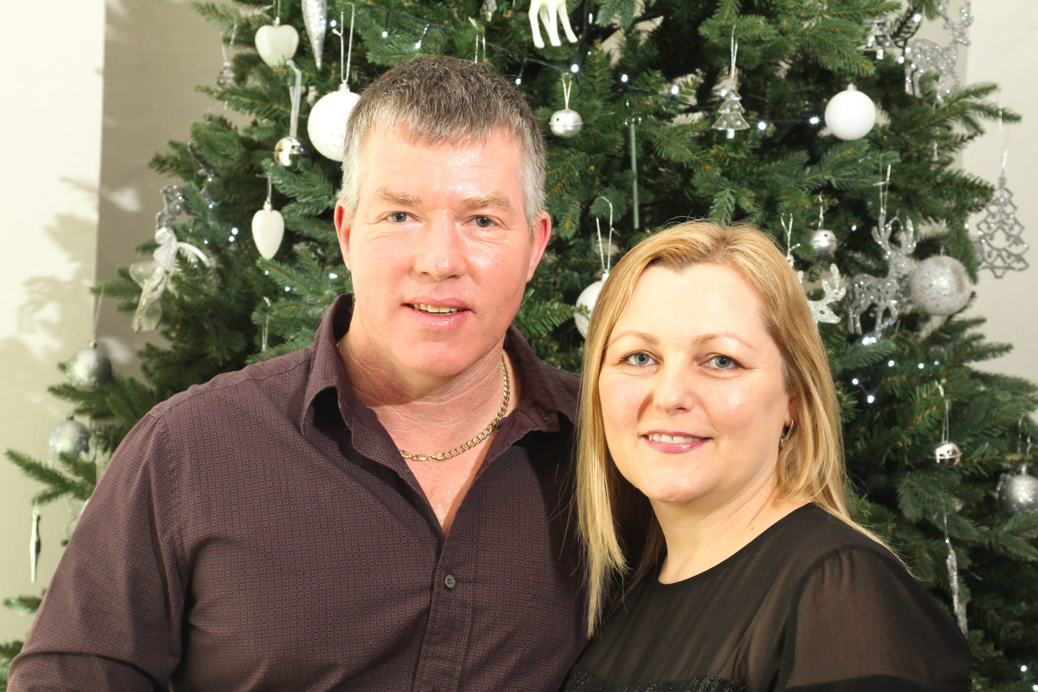 Friendly couple in front of Christmas tree at a Christmas party event